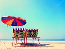 Stillstehende Stühle mit einem bunten Regenschirm auf einem sonnigen tropischen Strand stockfotografie