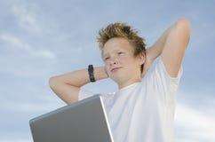 Stillstehender Jugendlicher mit dem Laptop, der wieder Hände hinter seinem Kopf anhält Stockfotografie