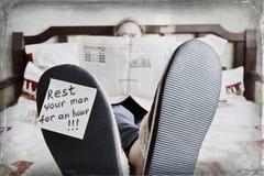 Stillstehender Mann, der im Bett liegt und Zeitung - Spaßkonzept liest stockbild