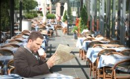 Stillstehender trinkender Kaffee und Lesen des Geschäftsmannes der Zeitung in der Gaststätte Stockbilder