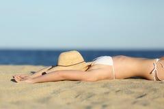 Stillstehendes Ein Sonnenbad nehmen der Frau auf dem Sand des Strandes mit einem Bildhut Stockfotografie