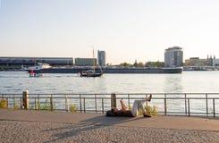 Stillstehendes Lügen der Frau auf dem Amstel-Flussufer gegen den Hintergrund des Hafens und des Hauptbahnhofs in Amsterdam lizenzfreie stockfotografie