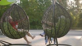 Stillstehendes Sitzen der Großmutter und des Großvaters auf hängenden Stühlen in der Sonne Gl?ckliche freundliche Familie Erholun stock video footage