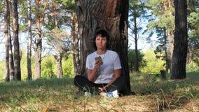 Stillstehendes Sitzen der jungen Frau durch einen Baum im Park und Hören Musik, die in Rhythmus sich bewegt Musik, Erholung im Fr stock video