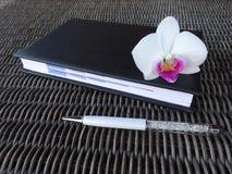 Stilo con l'ordine del giorno ed il fiore dell'orchidea Fotografia Stock Libera da Diritti