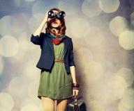 Stilrödhårig manflicka med binokulärt och resväskan royaltyfria foton