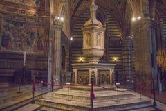 Stilsort i Siena Baptistery, med den marmortabernaklet och statyn av Jacopo della Quercia, panelen vid Ghiberti och tro av Donate Fotografering för Bildbyråer