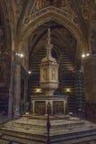 Stilsort i Siena Baptistery, med den marmortabernaklet och statyn av Jacopo della Quercia, panelen vid Ghiberti och tro av Donate Arkivfoton