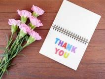 Stilsorten tackar dig på den tomma anteckningsboken och bukett av nejlikablomman Royaltyfria Foton