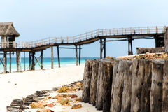 Stilt bridge to bungalow hut on tropical beach Stock Photos