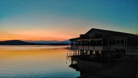 Stilt house on the lake at sunset. A palafitte on the lake of Viverone, near Torino and Biella in Piedmont, Italy royalty free stock photography