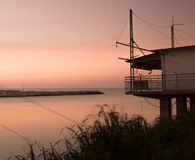 Stilt house on the sea in front of the sunset Stock Photo