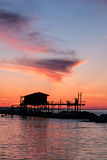 Stilt house in silhouette over the sea. During a beautiful red sunset Royalty Free Stock Photo
