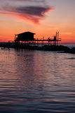 Stilt house in silhouette over the sea. In a beautiful red sunset Stock Images