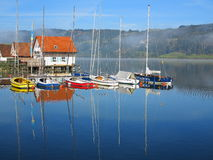 Modern stilt houses lake idyll. Morning idyll at lake with houses built on stilts and sailing boats anchored at the jetty. Picture taken in late summer royalty free stock image