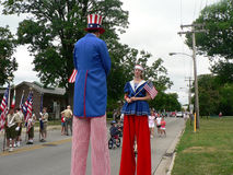 Stilt-walkers at Fourth of July parade. Winnetka, Illinois, United States - July 4, 2007: Stilt-walkers dressed as Uncle Sam and Lady Liberty wait to march in a Royalty Free Stock Images