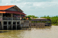 Stilted houses and the river, Philippines. Poor stilted houses and dirty river. Sky is cloudy Stock Photography