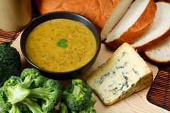 Stilton and broccoli soup. Bowl of broccoli and Stilton soup in kitchen setting surrounded by ingredients, crusty bread and butter Stock Photo
