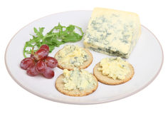 Stilton Cheese & Biscuits. Mature stilton cheese with oatcake biscuits, grapes and rocket leaves Royalty Free Stock Images