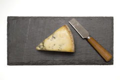 Cheese on slate board with knife Stock Photo