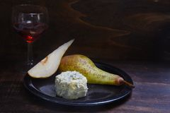 Stilton cheese, pears and red port wine on a dar rustic wooden b Stock Photos