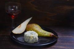 Stiltonkäse, Birnen und roter Portwein auf einem dar rustikalen hölzernen b Stockfotos