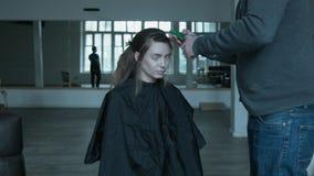 Stiltsit人做一个美好的年轻模型的发型 生产商在关于组织的电话谈话 影视素材