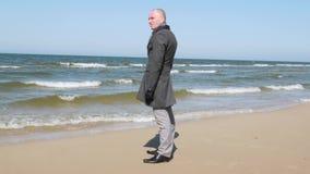 Stilvoll gekleidete Mannstellung auf dem Strand des Meeres und über dem Horizont sicher schauen Die goldene Taste oder Erreichen  stock video