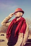 Stilvoll gekleideter, bärtiger Mann im lustigen Hut, der in einer Küste steht Stockbild