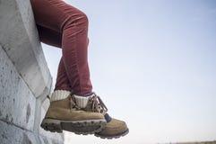 Stilvoll gekleidetes Mädchen sitzt das Baumeln und die Kreuzung ihrer Beine auf a stockfotografie
