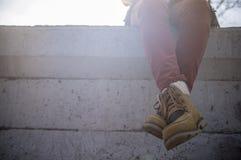 Stilvoll gekleidetes Mädchen sitzt das Baumeln und kreuzte ihre Beine auf Wechselstrom stockfoto