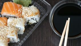 Stilvoll gelegte Sushi stellten auf einen schwarzen hölzernen Hintergrund nahe bei Sojasoße und chinesischen Bambusstöcken ein Ve stock footage