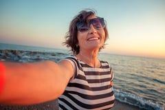 Stilvolle attraktive reife Frau 50-60 macht selfie auf beweglichem pho Lizenzfreie Stockfotos