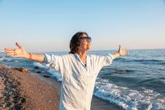 Stilvolle attraktive reife Frau 50-60 mit den offenen Armen auf den Meeren Stockfotografie