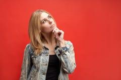 Stilvolle attraktive schlanke junge blonde Studentenfrau hält durchdacht ihr Kinn und schaut oben mit einem nachdenklichen Ausdru lizenzfreies stockbild