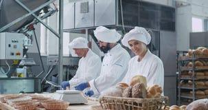 Stilvolle Bäcker der schönen Bäckereifabrik zwei Männer und eine Frau, die Stücke arbeitet Teig für backendes Brot zusammen, bild stock video footage