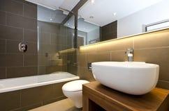 Stilvolle Badezimmerreihe mit drei Stücken mit dunklen Fliesenwänden stockfotografie