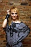 Stilvolle blonde Frau auf Backsteinmauerhintergrund Stockfoto