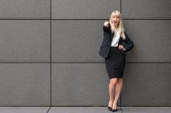 Stilvolle blonde Frau, die auf die Kamera zeigt Lizenzfreie Stockfotos