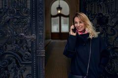 Stilvolle blonde Frau, die in einem aufwändigen historischen Eingang steht Stockbild