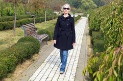 Stilvolle blonde Frau, die innen in Park geht Stockfoto