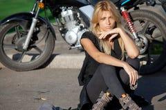 Stilvolle blonde Frau, die nahe Motorrad sitzt Lizenzfreie Stockfotos