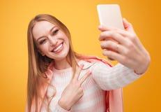 Stilvolle blonde Frau, die selfie auf Orange nimmt Lizenzfreies Stockbild