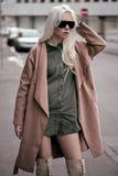 Stilvolle blonde junge Frau, die draußen aufwirft Stockbild