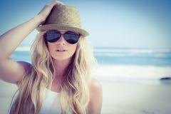 Stilvolle blonde schauende Kamera auf dem Strand Lizenzfreie Stockbilder