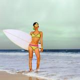 Stilvolle blonde Stellung auf dem Strand mit Brandungsbrett Stockfotos