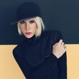 Stilvolle Blondine in der schwarzen Kappe und im schwarzen Hemd Stockfotos
