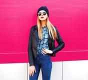 Stilvolle Blondine des Modeporträts in der Felsenschwarz-Artjacke, Hut, der auf Stadtstraße über bunter rosa Wand aufwirft stockbilder