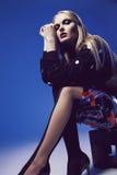 Stilvolle Blondine, die in den Strumpfhosen und in der schwarzen Spitze sitzen Lizenzfreies Stockbild