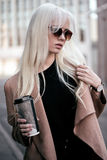 Stilvolle Blondine, die draußen mit Kaffee aufwerfen Stockbilder